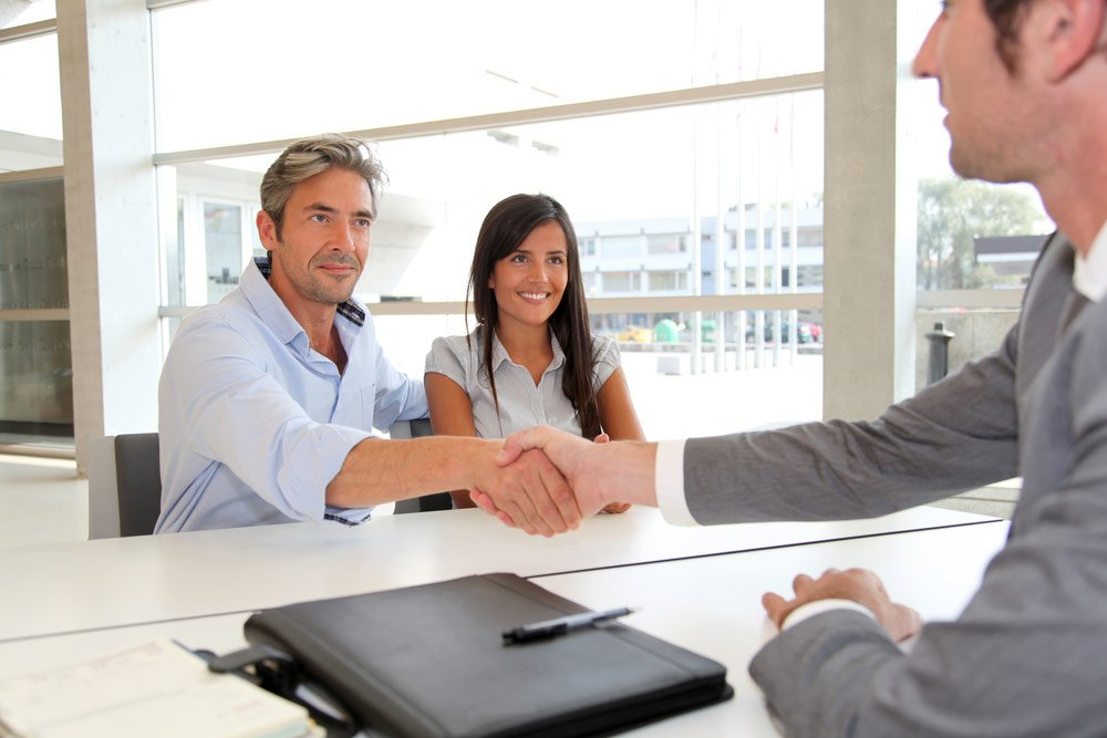 Couple handshaking with business man
